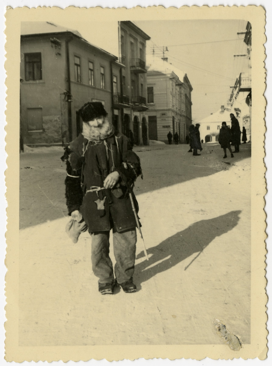 Close-up portrait of a destitute Jewish man standing on a street of the Krosno ghetto.