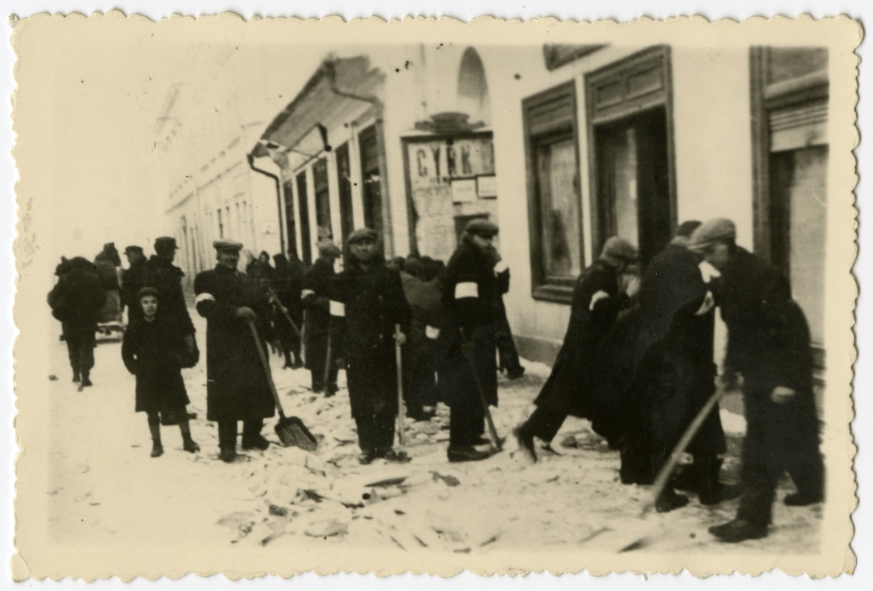 Jewish men shovel up debris on a street in the Krosno ghetto.