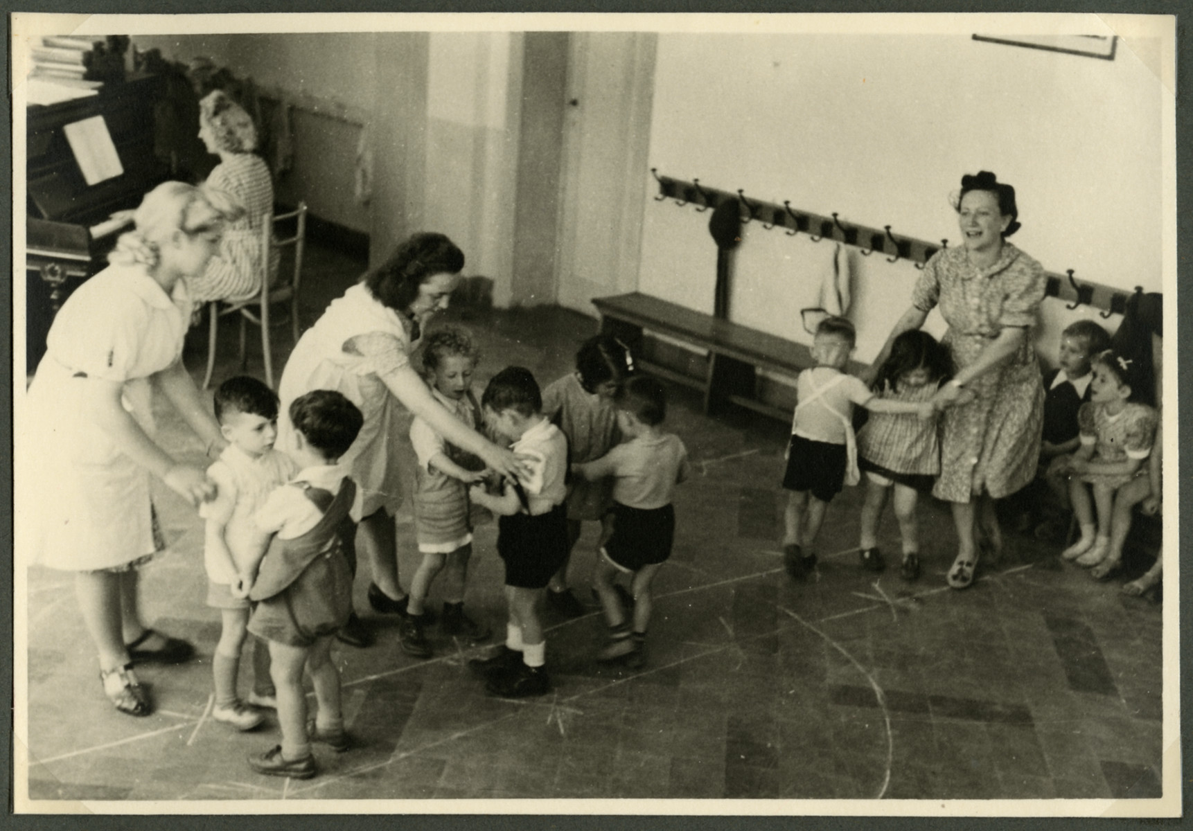 Staff of the Nos Petits children's home dance with the children.