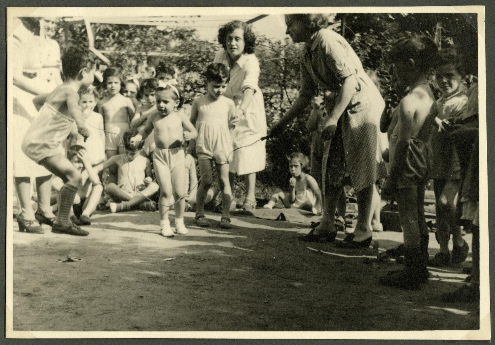 Children from the Nos Petits children's home in Belgium jump rope in a garden.