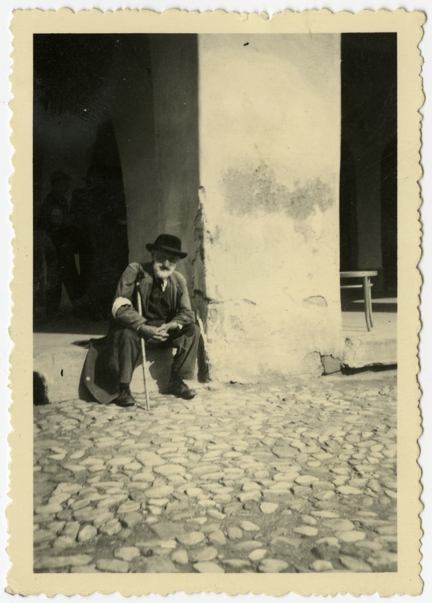 A Jewish man sits on a door stoop in the Krosno ghetto.