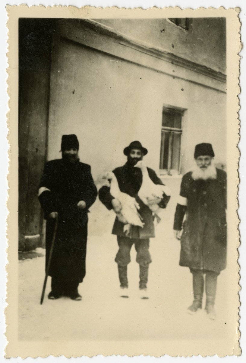 Portrait of three religious Jews, one holding a pair of geese, in the Krosno ghetto.
