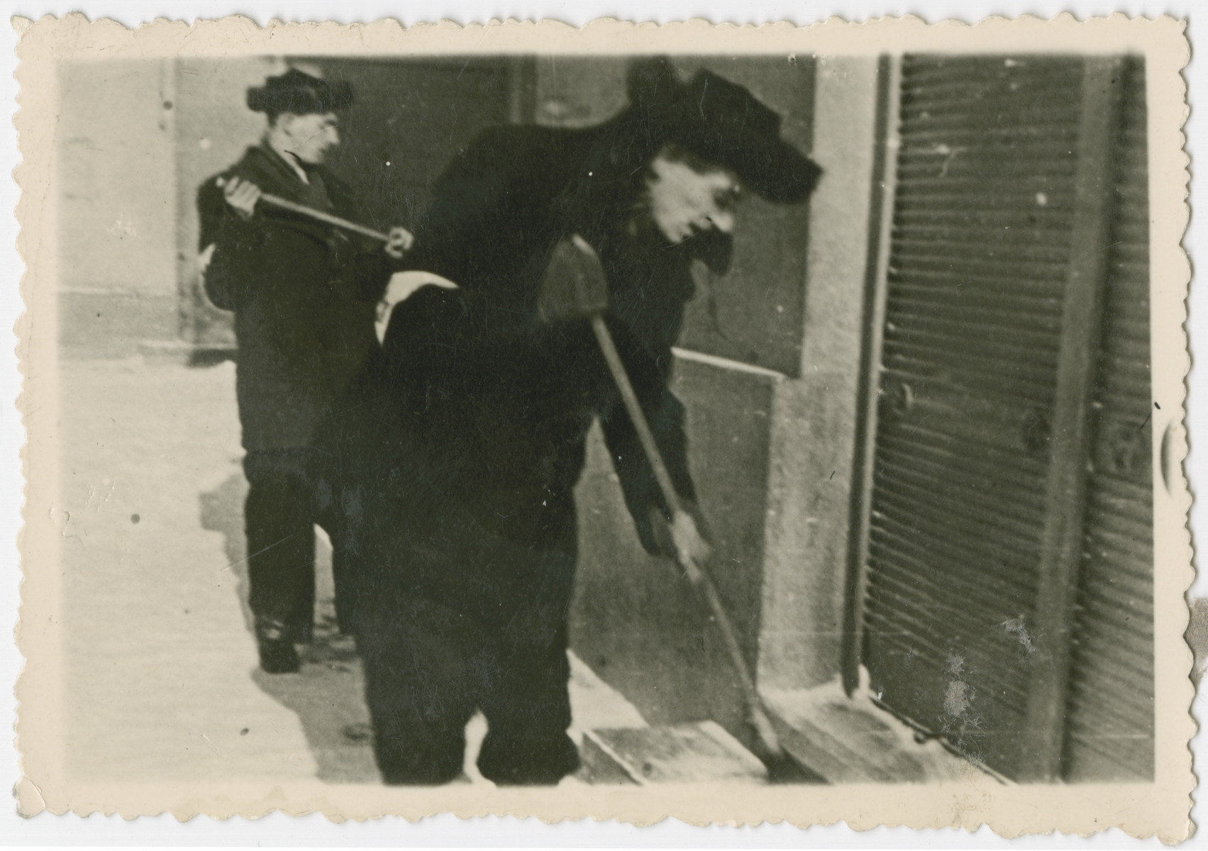 Two Jewish men shovel snow in the Krosno ghetto.