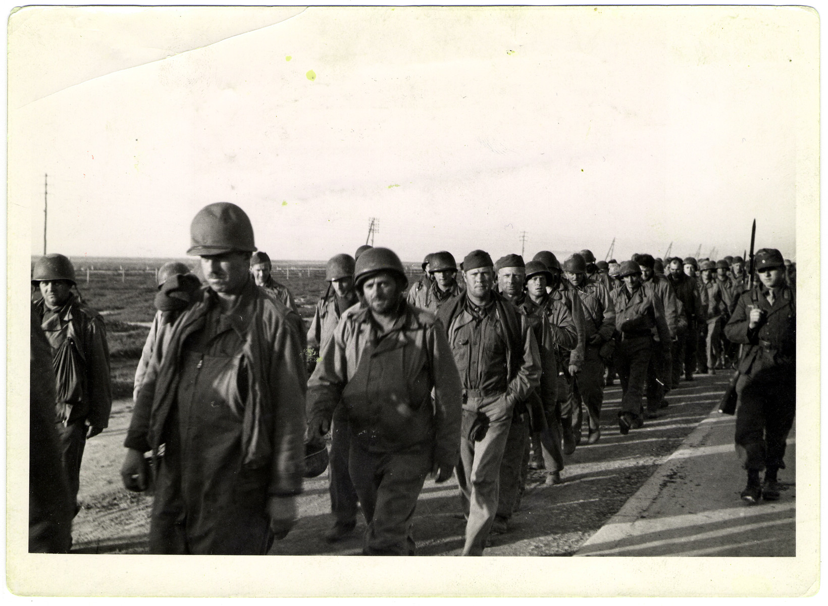 A column of American prisoners march along a road after having been captured by German soldiers.   This photograph was found by the donor, a former Captain in the U.S. Army, on the floor of the Propaganda Ministry in Berlin in August 1945.