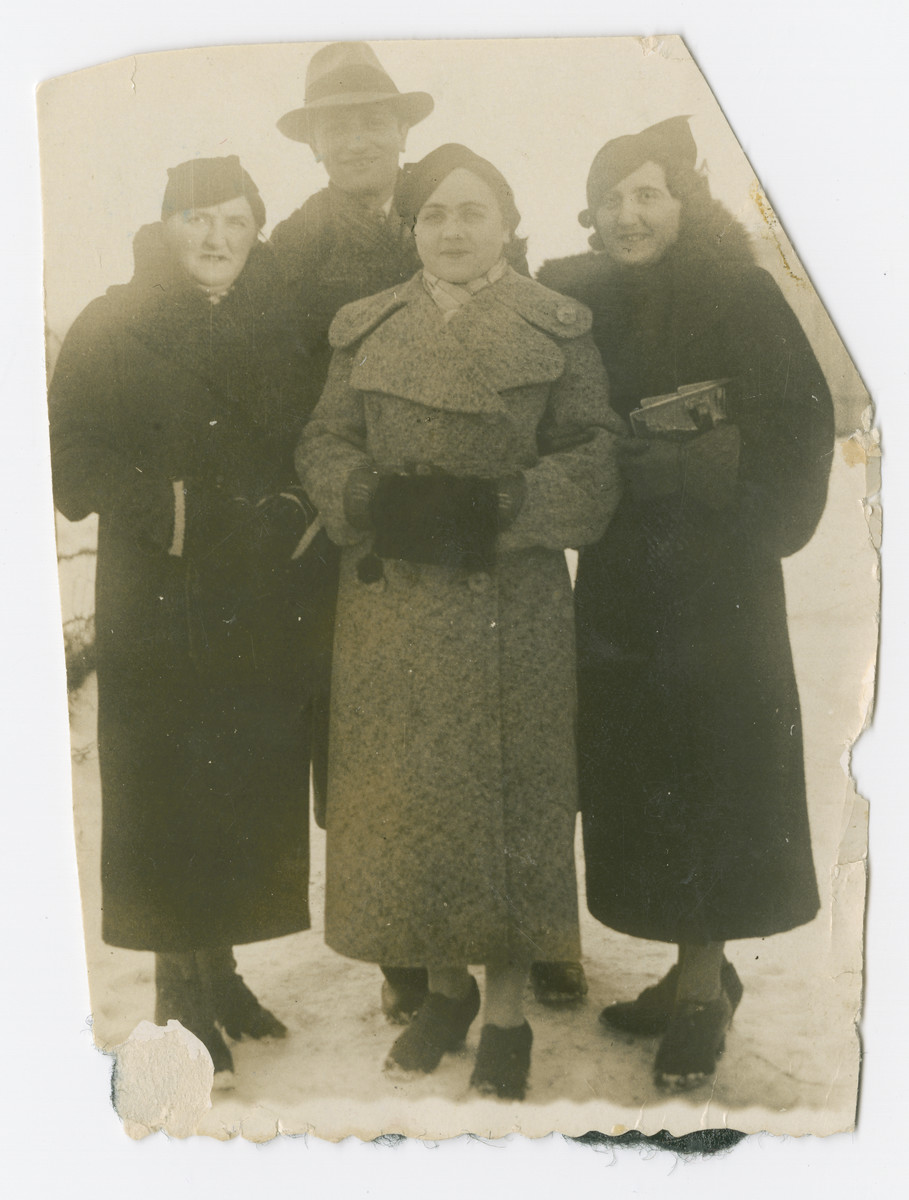 Gita (standing left) and Mendel Kuperman (center) pose for a portrait with two unidentified women.