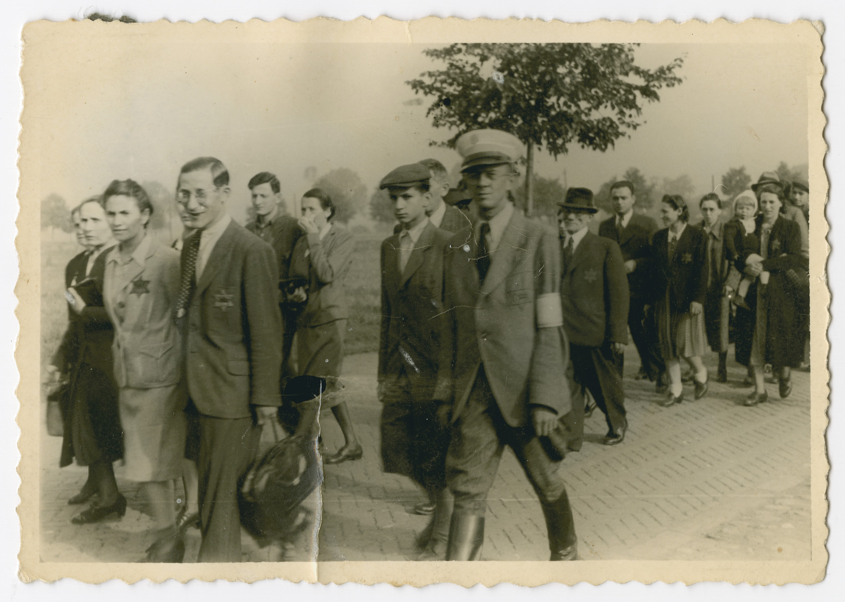 Jews march down a street in Bedzin accmpanied by a Jewish policeman.  Henri and Esther Borzykowski (nee Fiszer) pictured in the back right walk in a line during their time in Bedzin. The two married before the war and survived the camps. Esther's father Srul Fiszer is pictured in front of the couple in a top hat.