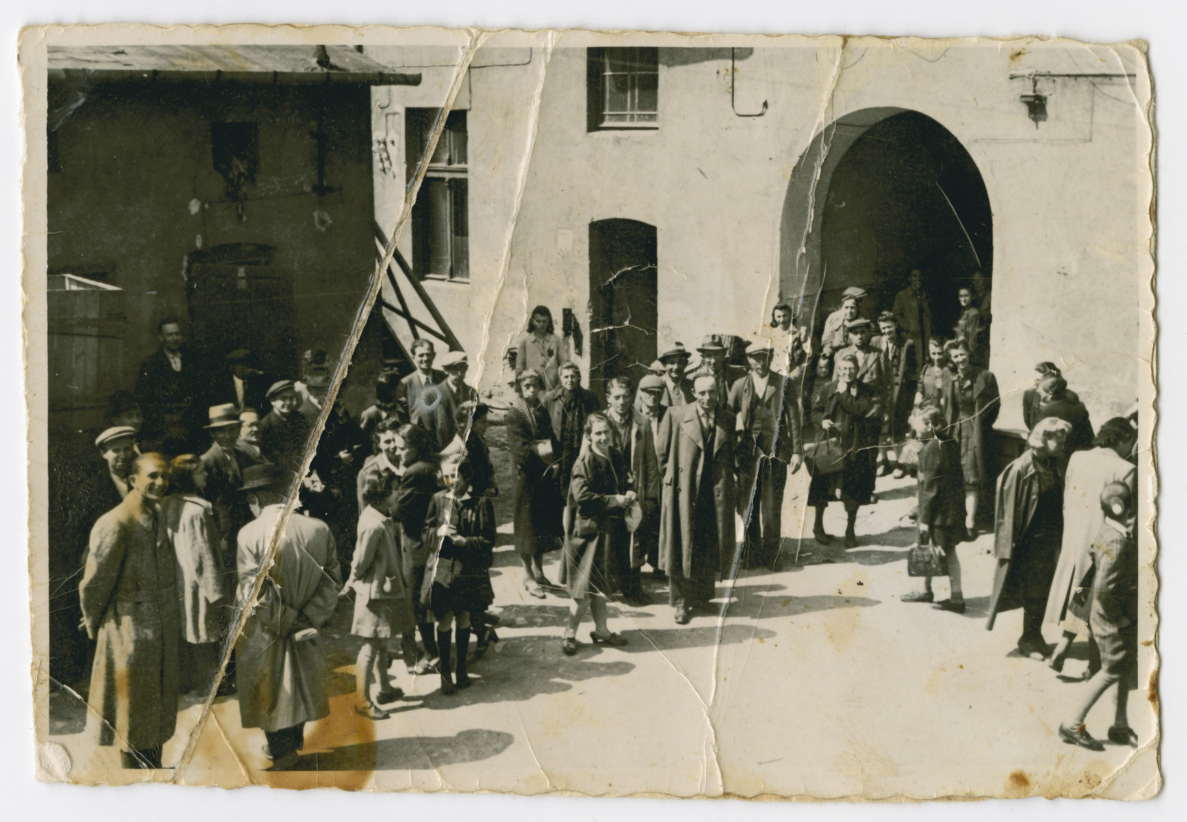 A group of men, women and children gather in a courtward in Bedzin.  Wolf Fiszer is pictured in the front left.  Hannah Gilbert Fiszer is pictured second from the right.  Shye was his first wife and later perished in Auschwitz.