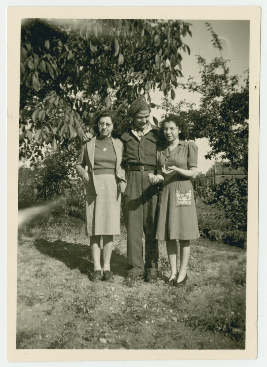 Three young adults pose in a garden in s Heerenberg after the war.  Dini Straus is on the left.  Betty Straus is on the right and a neighbor wearing a uniform stands in the middle.