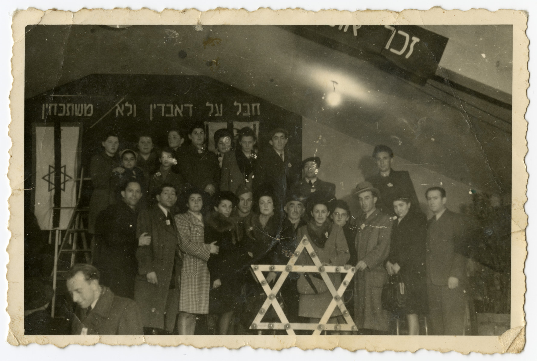 Group portrait of Jewish displaced persons in the Landsberg camp at a memorial service.  They are standing behind a large Star of David and the banner in the back tells them not to forget.