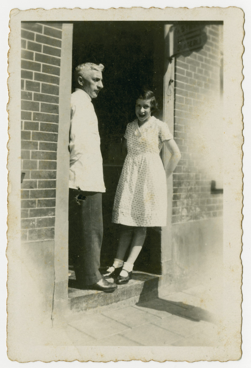 Benjamin Straus and his daughter Betty stand at the entrance of their house.