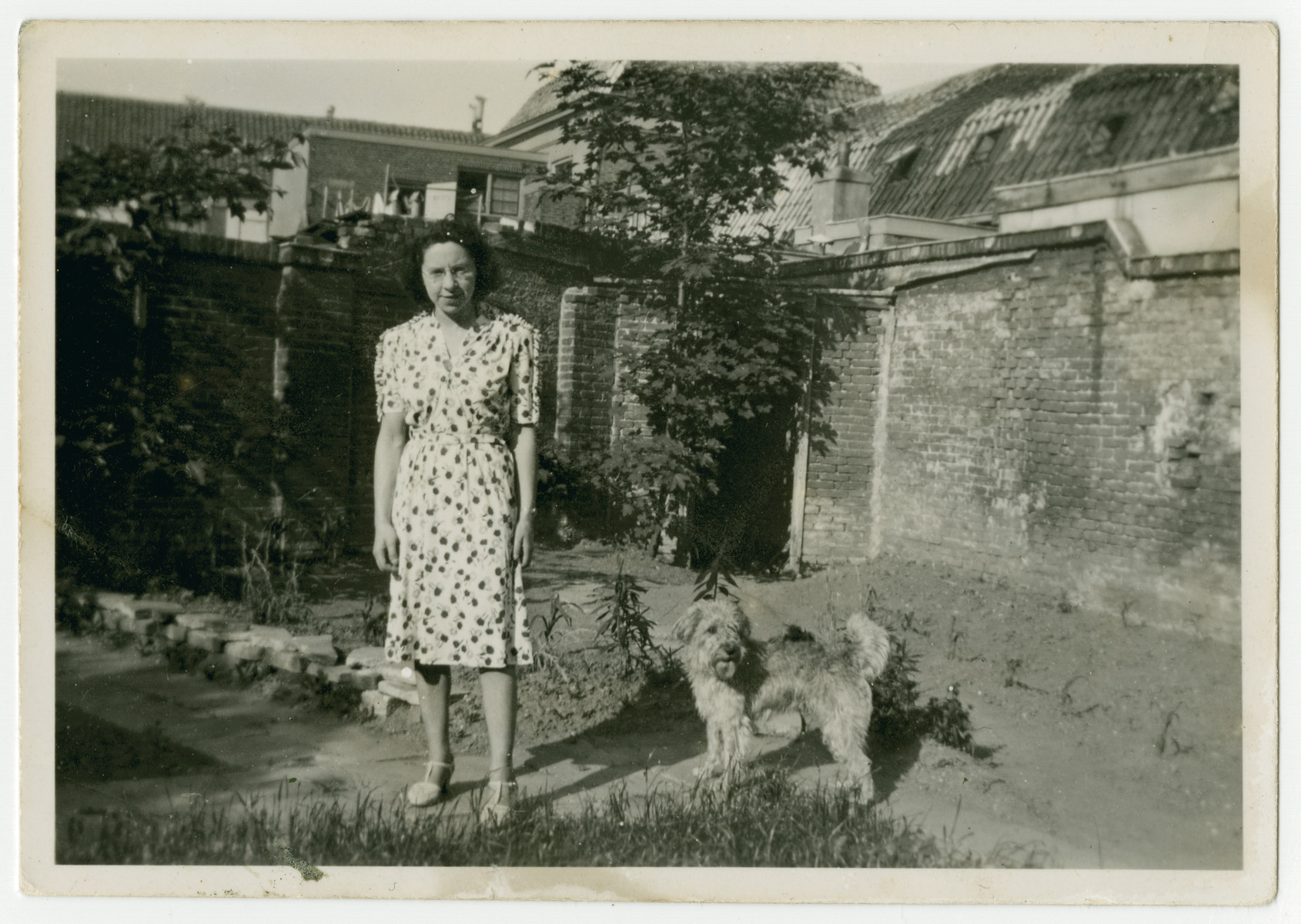 Betty Straus poses with her dog in a garden in Utrecht.