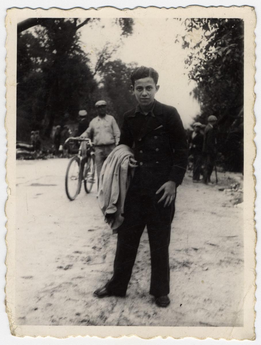 Moniek Spiro (now Marc Spiro) stands on a dirt lane in  Stowiki (Slowiki), Poland near Kielce.