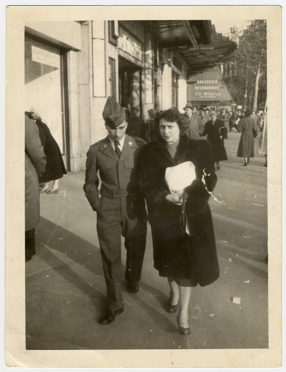 Marcel Hodak walks down a street in Paris with his ousin Eva Pelc.  Marcel was a French Jew who had immigrated to the United States after the war and returned as a serviceman in the U.S. army.
