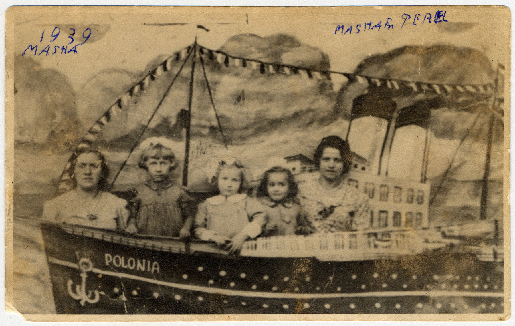 Studio portrait of women and children from Jewish family in Lodz posing against a mock boat,  The original Yiddish caption reads: