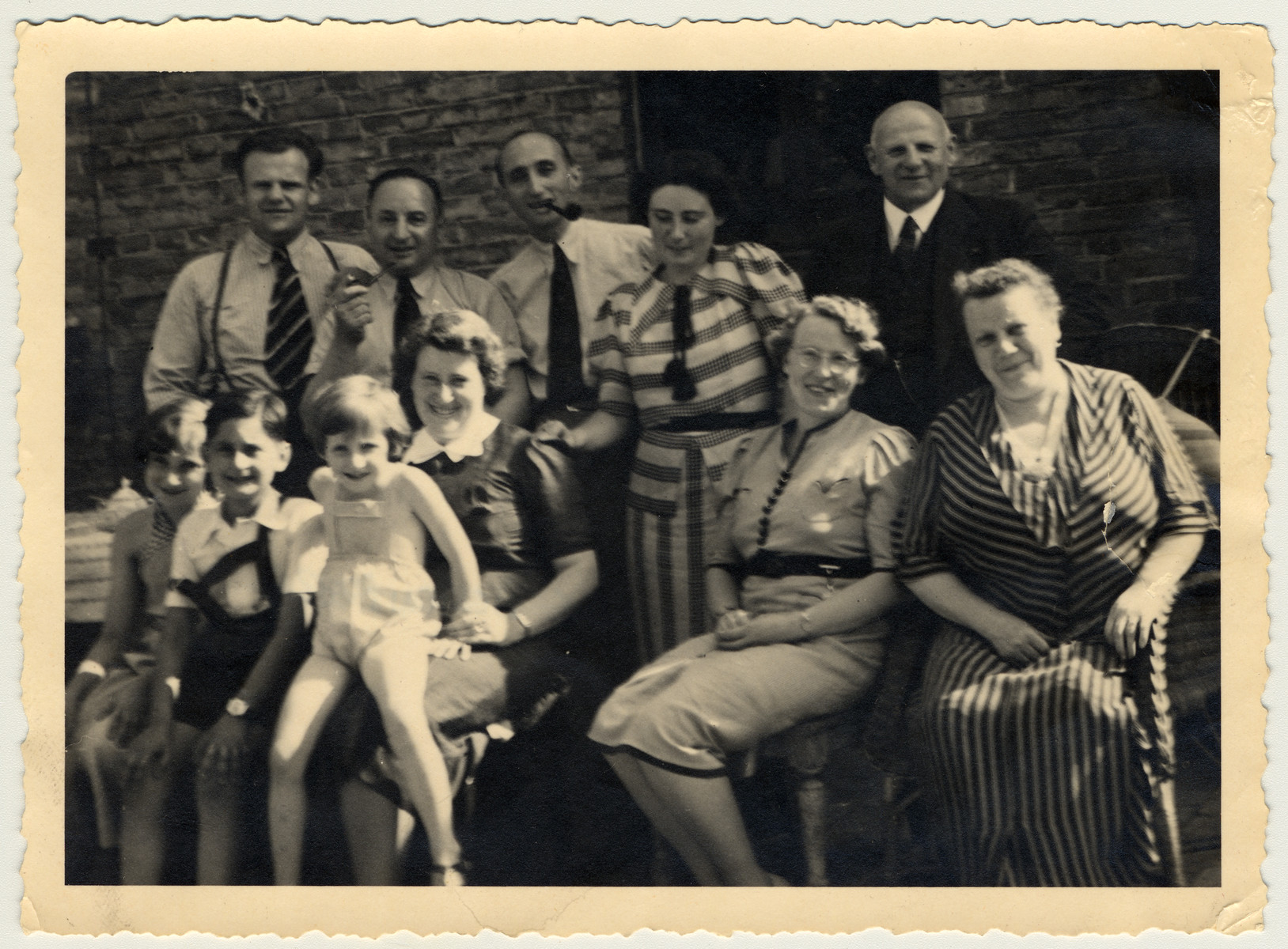 """The Heimann and Dublon families gather for a family photograph.  Front row (L to R, seated): Lore Dublon, Peter Heimann, """"Fife"""" Dublon (Lore's sister), Lili Doernberg, Ernie Dublon(mother of the girls), and unknown.  Rear Row (L to R, standing): Unknown, Solomon Heimann (father of Peter), Willy Dublon (husband of Ernie), Unknown, Unknown."""