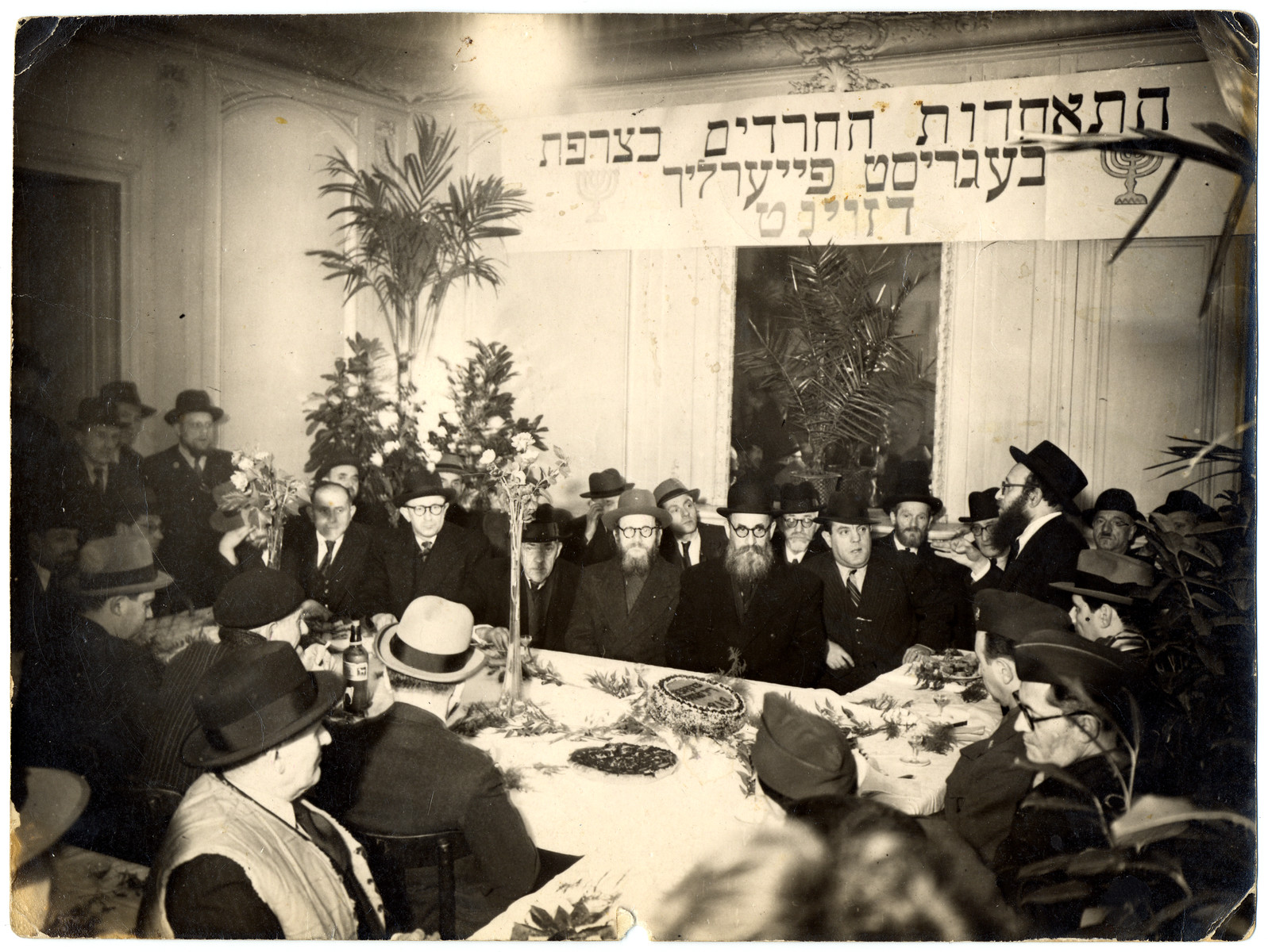 French rabbis and religious leaders gather for a meeting of the Association of Orthodox Jews (AIP) in France after the war.  Rabbi Zalman Schneerson is seated in the center of the table.