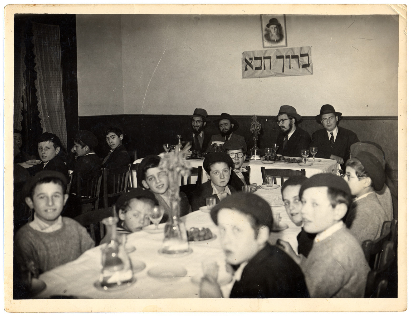 "Young religious Jewish boys sit around a table at the Yeshiva of Eragny, headed by a group of rabbis, including Rabbi Zalman Schneerson.  On the war is a sign in Hebrew that says ""welcome.""  The young boy with his eyes half closed, behind a glass cup, has been identified as Shimon Lazaroff (later Rabbi Shimon Lazaroff, Director of Chabad Lubavitch of Texas)"
