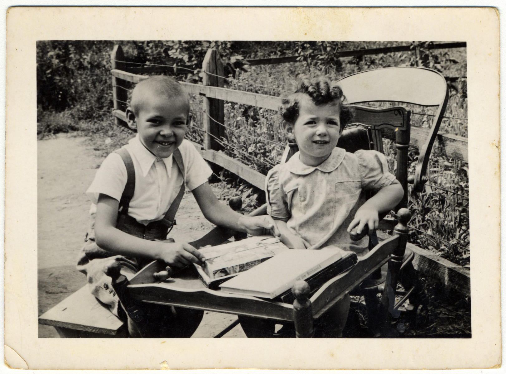 Two young children sit at an outdoor table by a fence.  Karla Fortes is sitting on the right.