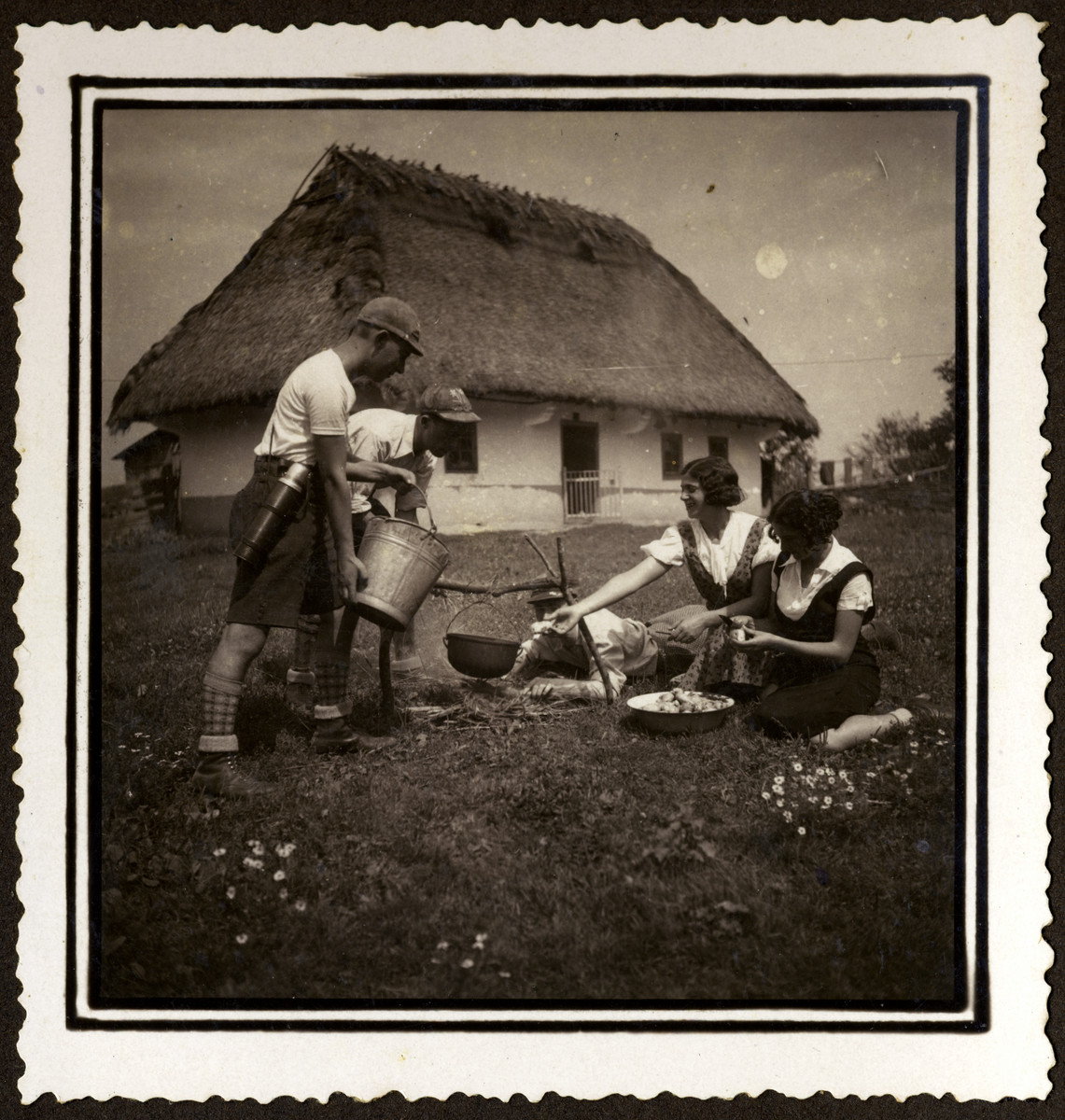 Four Romanian Jewish youth cook a meal outdoors while on an excursion to the countryside.    Miriam Segal is third from left.