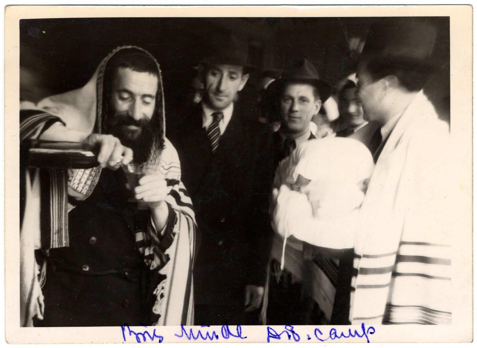 A mohel pours a glass of wine in advance of performing a brit milah (ritual circumcision) in the Feldafing displaced persons' camp.