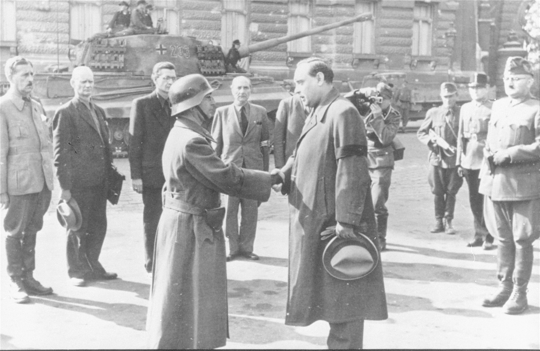 The new premier of Hungary, Arrow Cross party leader Ferenc Szalasi, greets his troop commander in front of the Ministry of Defense in Budapest.    Pictured behind them (from left to right) are Jeno Szollosi (Deputy Prime Minister); Emil Kovarcz (minister in charge of mobilization and war readiness); Ferenc Kassai Schallmayer (Minister of Propaganda and National Defense), Gabor Vajna (Minister of the Interior); a German SS photographer; a member of the Hungarian military police; an Hungarian police official; and Karoly Beregfy (Minister of Defense).   In the background is a German tank.  After Horthy's announcement of peace talks with the Soviets, armed Arrow Cross units, with German assistance, took control of strategic positions within the capital: the offices of Hungarian radio, military bases and checkpoints, and the entire castle district, which includes the residence of the Regent and all government ministries.  During the coup, members of Horthy's bodyguard unit put up resistance, resulting in the introduction of German tanks and heavy artillery into the capital to secure the new government and to put pressure on Horthy to resign.