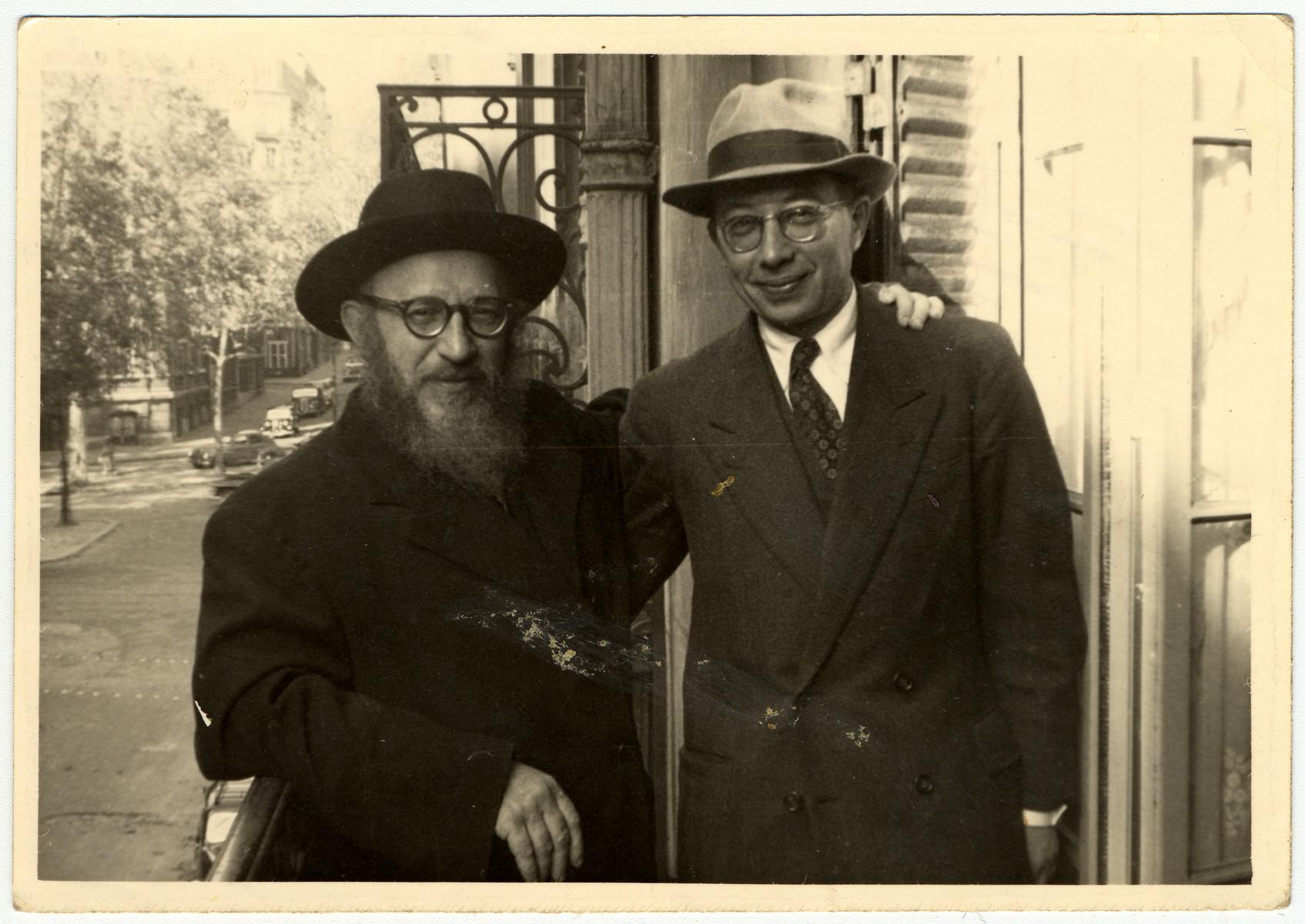 Rabbi Zalman Schneerson and Rabbi Kotujanski pose on a balcony in Paris after the war.