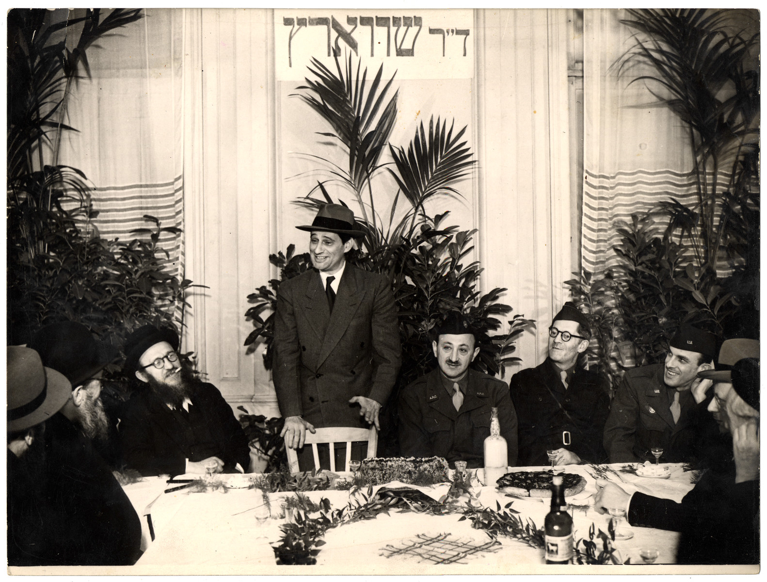 Joseph Schwartz, the European director of the Joint Distribution Committee, addresses a meeting of the Association of Orthodox Jews (AIP) in France after the war.  Rabbi Zalman Schneerson is seated to his left.