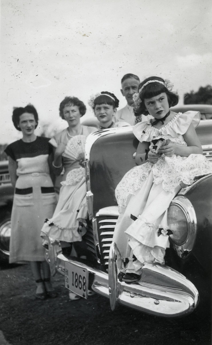 Postwar photo of Eva Meinberg dressed for Mardi Gras and sitting on an automobile.