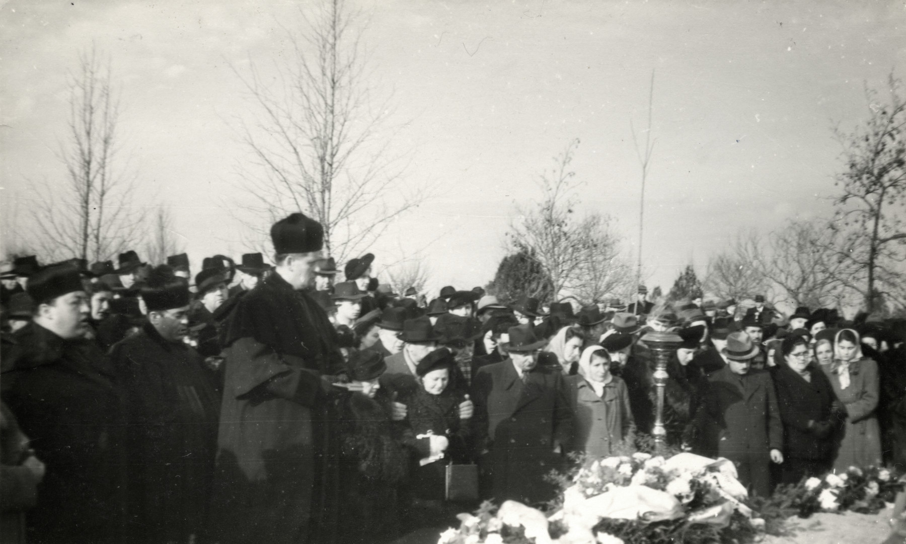 Rabbi Jeno Frenkel leads a memorial service following the exhumation and reburial of Jewish Holocaust victims.  Their bodies were exhumed in Strasshof\ and reburied in Szeged, Hungary.  Among those attending is Pal Gyulai, a survivor  who worked with Rabbi Frankel on this project to return victims remains from Strasshoff, Austria.