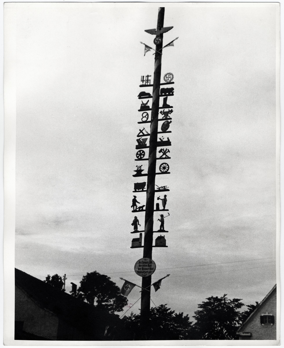 View of a maypole used as a part of the Harvest Festival and decorated with Nazi symbols.