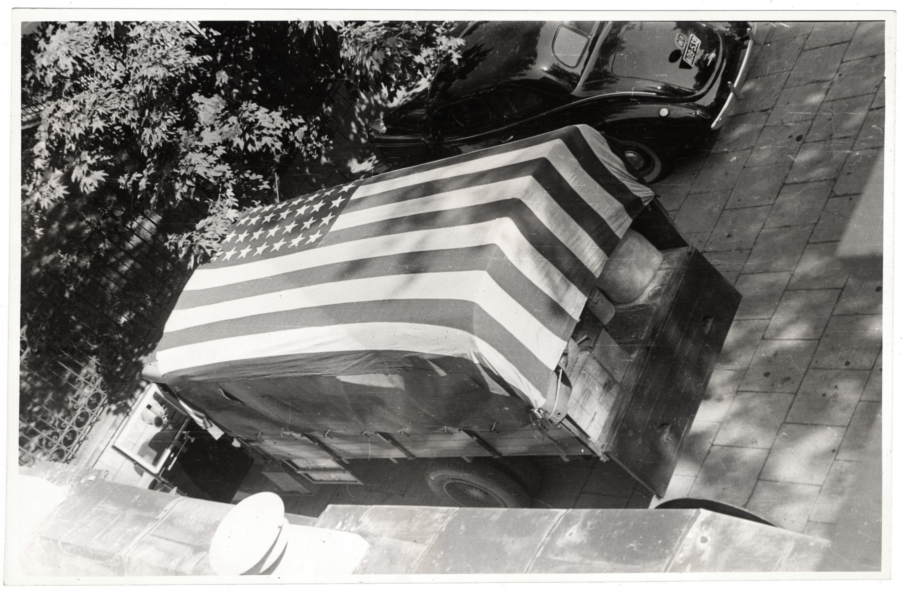 Aerial view of a truck filled with supplies and covered by an American flag in besieged Warsaw.
