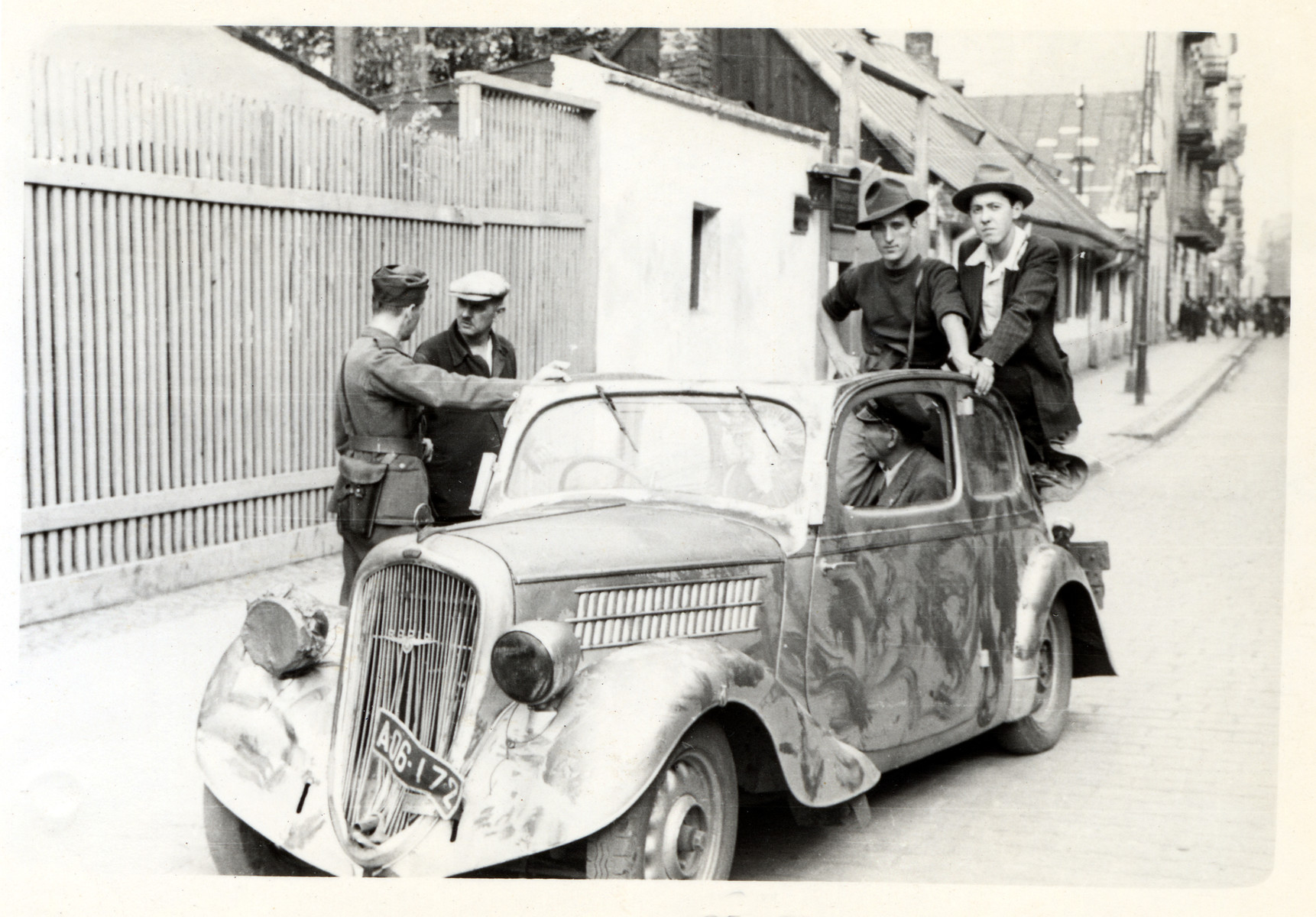 Polish civilians and a soldier loiter about an automobile [possibly Julien Bryan's car] in besieged Warsaw.