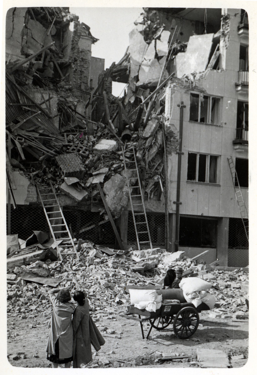 Two Polish women look at the destruction of an apartment building in besieged Warsaw.