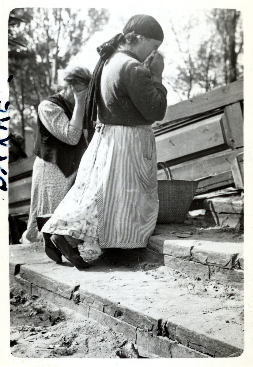 Polish women bow their heads and kneel in prayer after the destruction of their church in besieged Warsaw.
