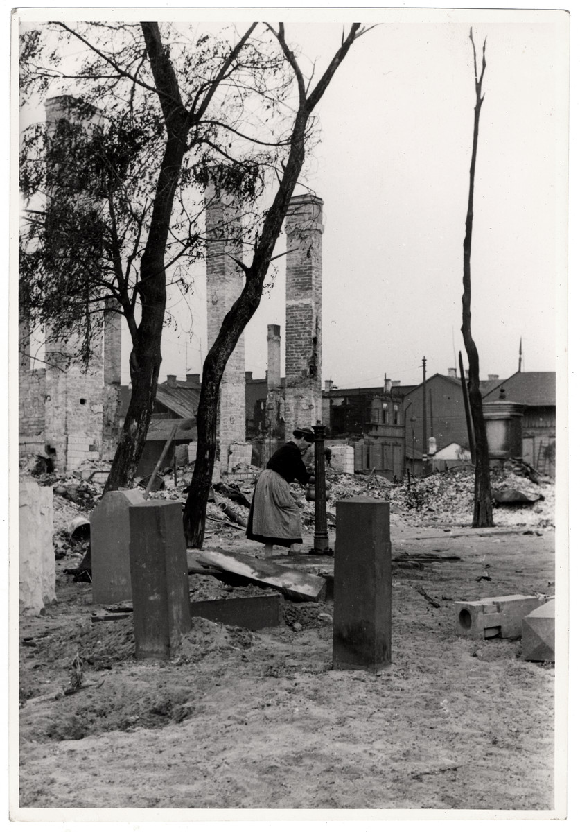 A Polish woman pumps water among the ruins of besieged Warsaw.