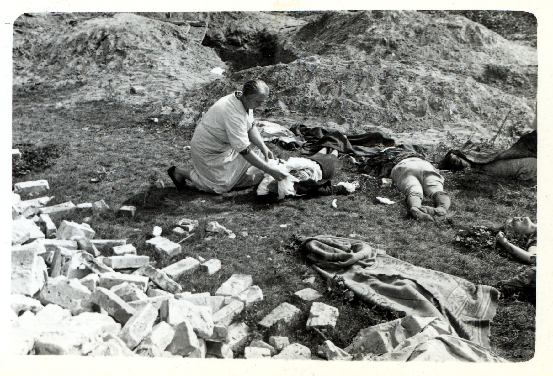 A Polish nurse attends to corpses lying on the ground in besieged Warsaw.