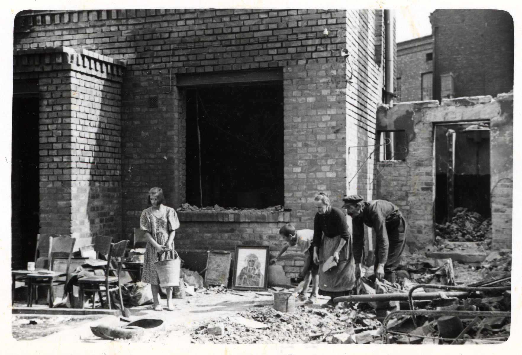 A Polish family picks up the pieces of the wreckage of a bombed out home in the besieged city of Warsaw.