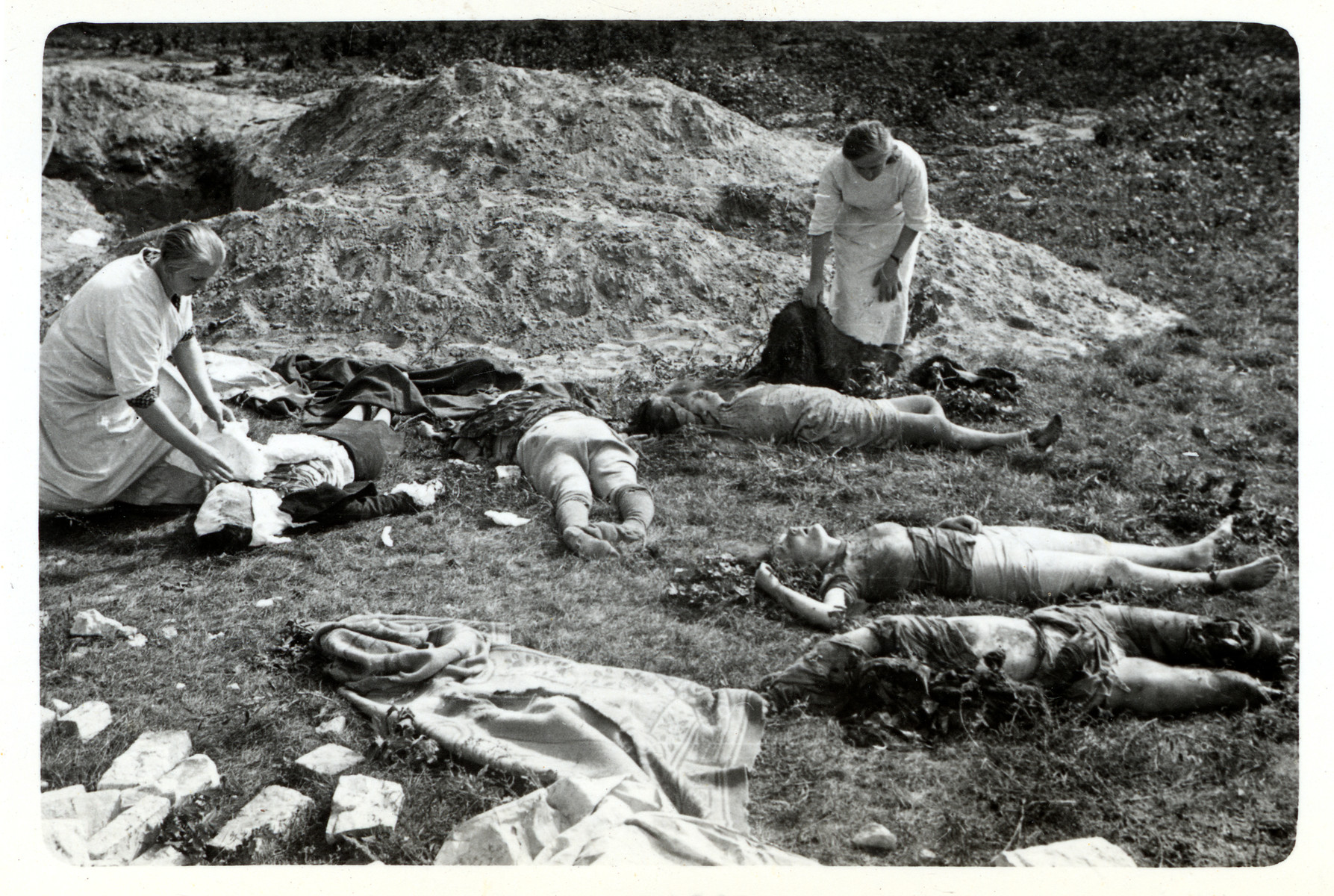Two Polish nurses attend to corpses lying on the ground in besieged Warsaw.
