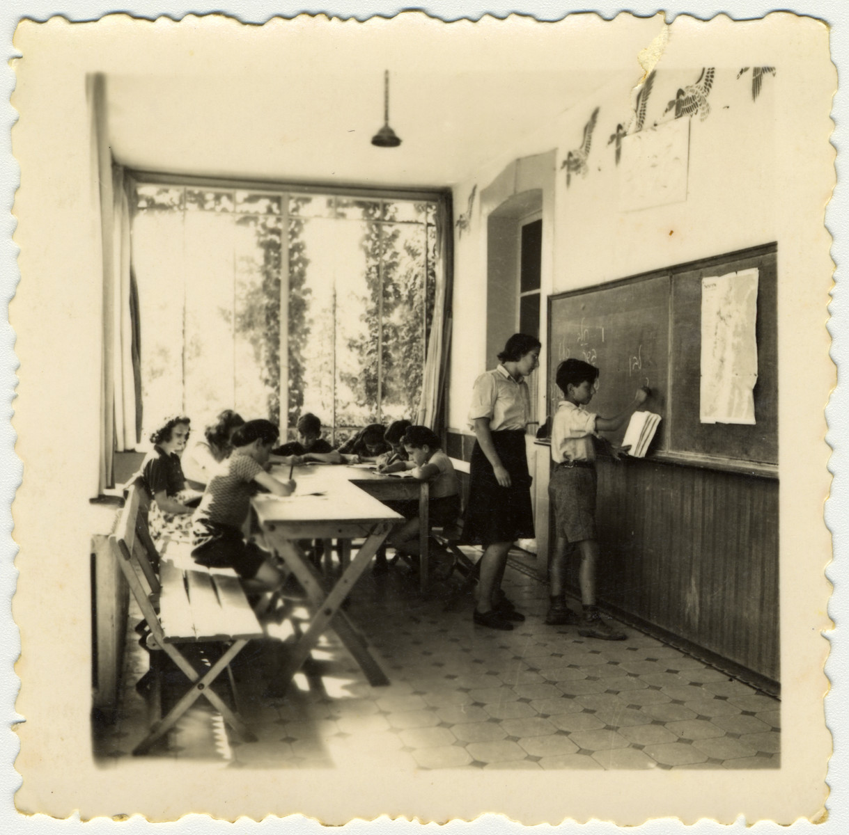 A boy writes Hebrew on the blackboard in a classroom of the Versoix children's home.