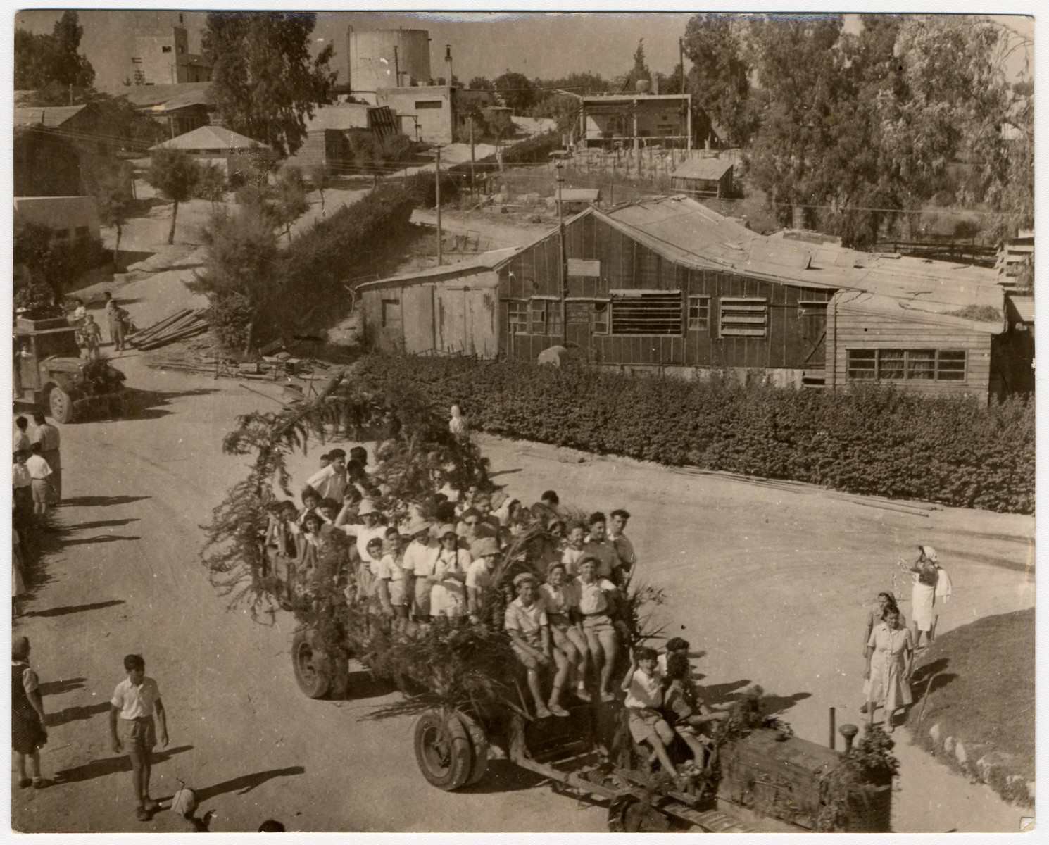 """Teenagers ride on a decorated tractor-pulled wagon to celebrate the harvest festival """"Chag HaBikkurim"""" (Shavuot) on Kibbutz Givat Brenner.  Daniel Barnea is pictured sitting on the wagon on the left."""
