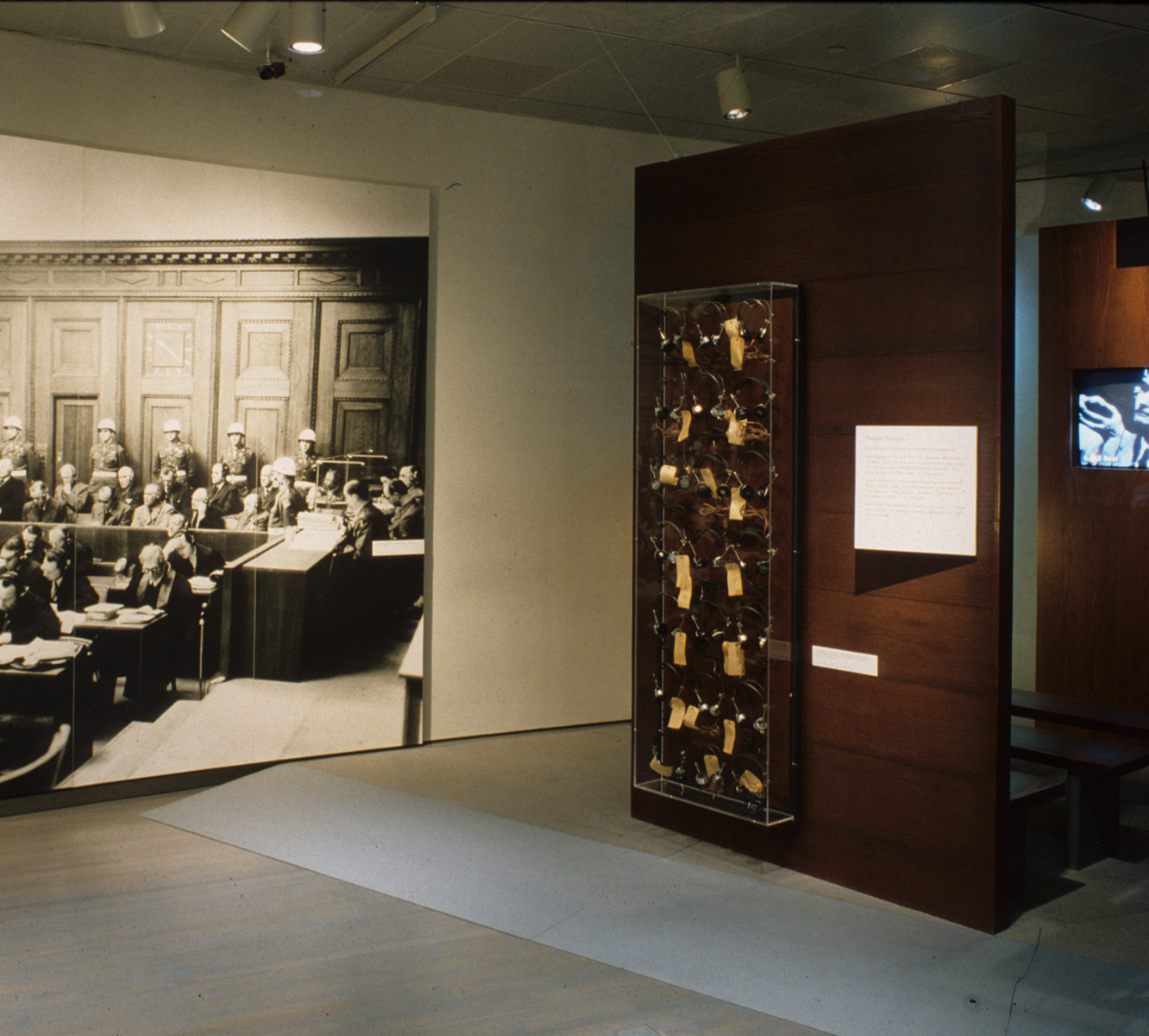 Installation photograph of the special exhibition, Liberation 1945.  This image shows the segments:  Pursuing the Killers, a view of theater, the perpetrator's head phones and a large mural photograph of the perpatrators in the courtroom at Nuremberg.
