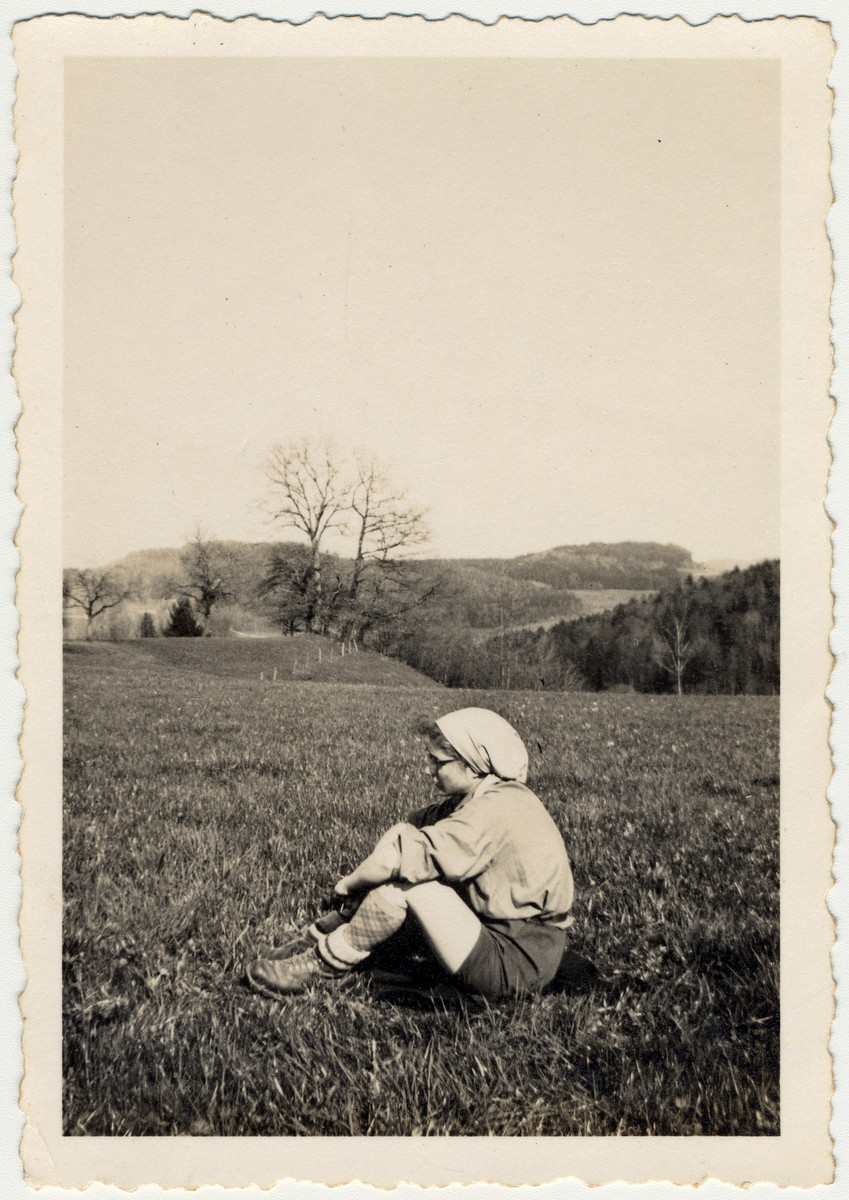 Minni Pickholz, a member of the Zionist youth movement, sits lin an open field probably in Elgg.
