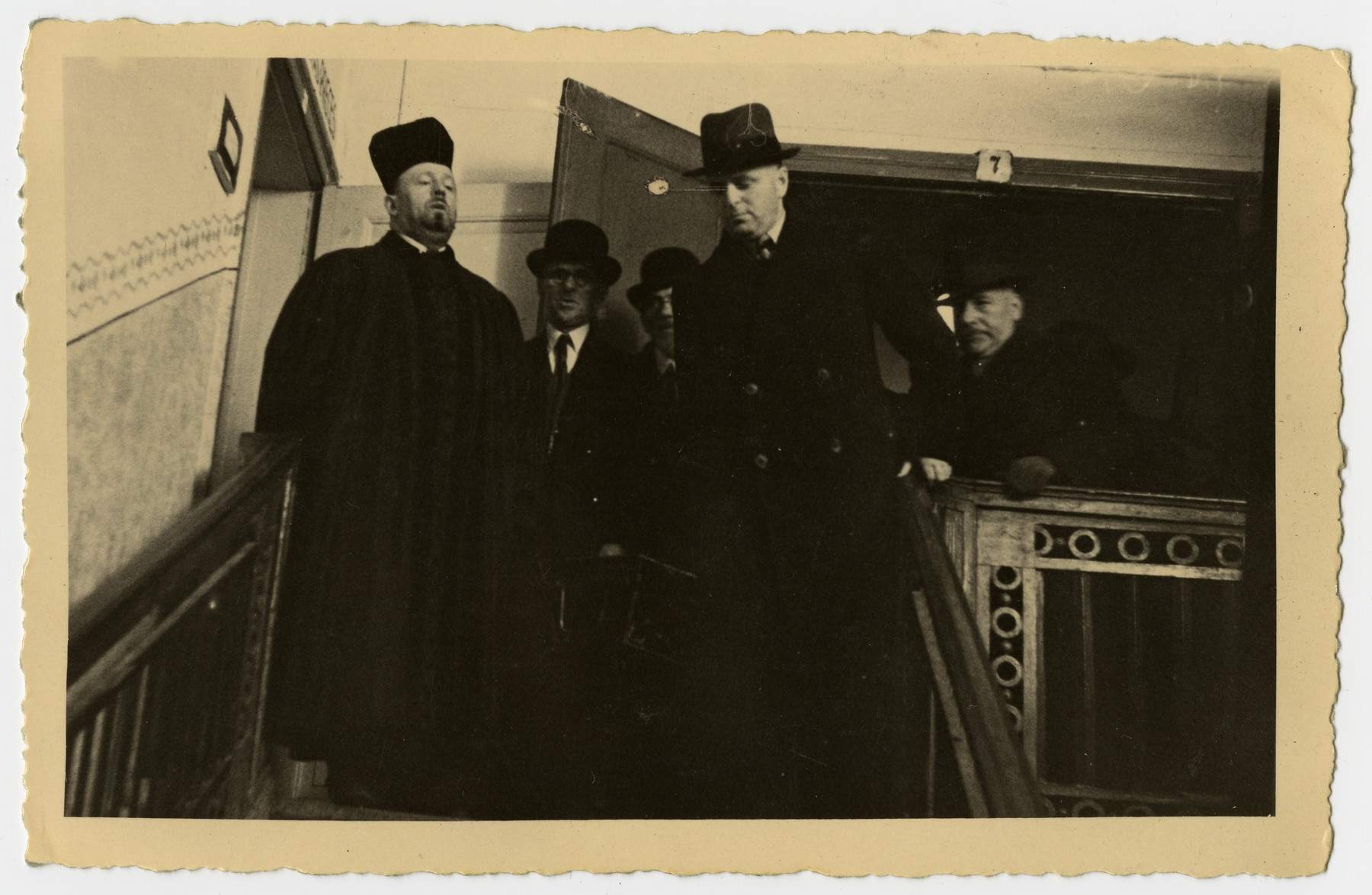 A cantor leads a porcession in prayer as the body of Freida Albin is carried down the stairs.  Pictured in the front is  the husband of Rosa Preiss, and Mr. Rosenthal is in the back.