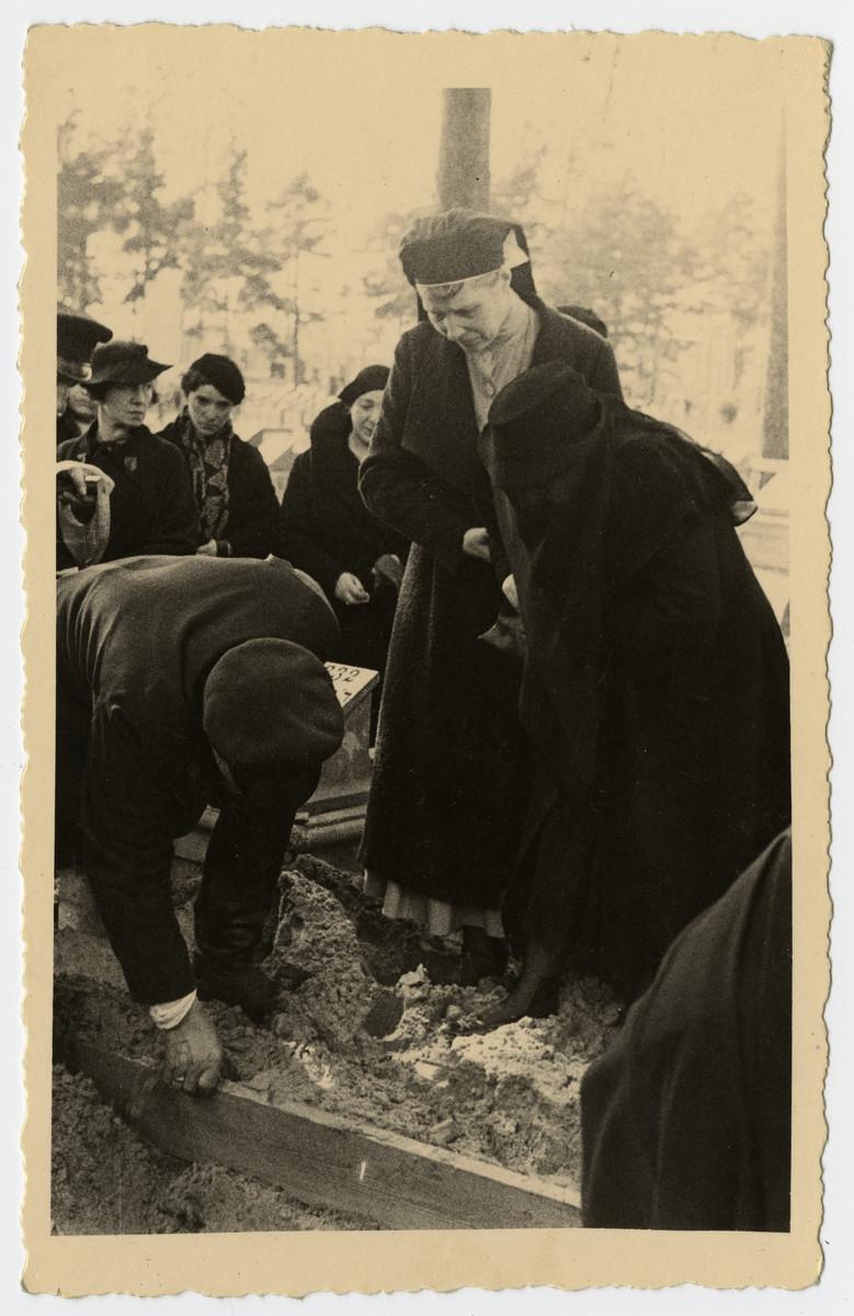 Berta and Nurse Anastasia tamp down the earth of the grave of Freida Albin.