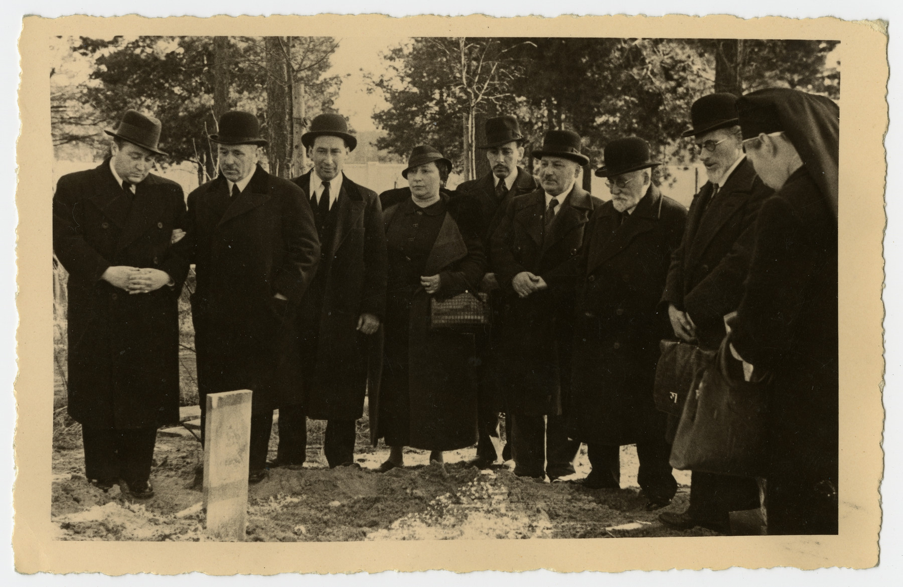 Mourners stand by the grave of Freida Albin.  Pictured are Papa, Aron, Zilla, Harri, Abraham, Opapa, an aquaintance, and a nurse.