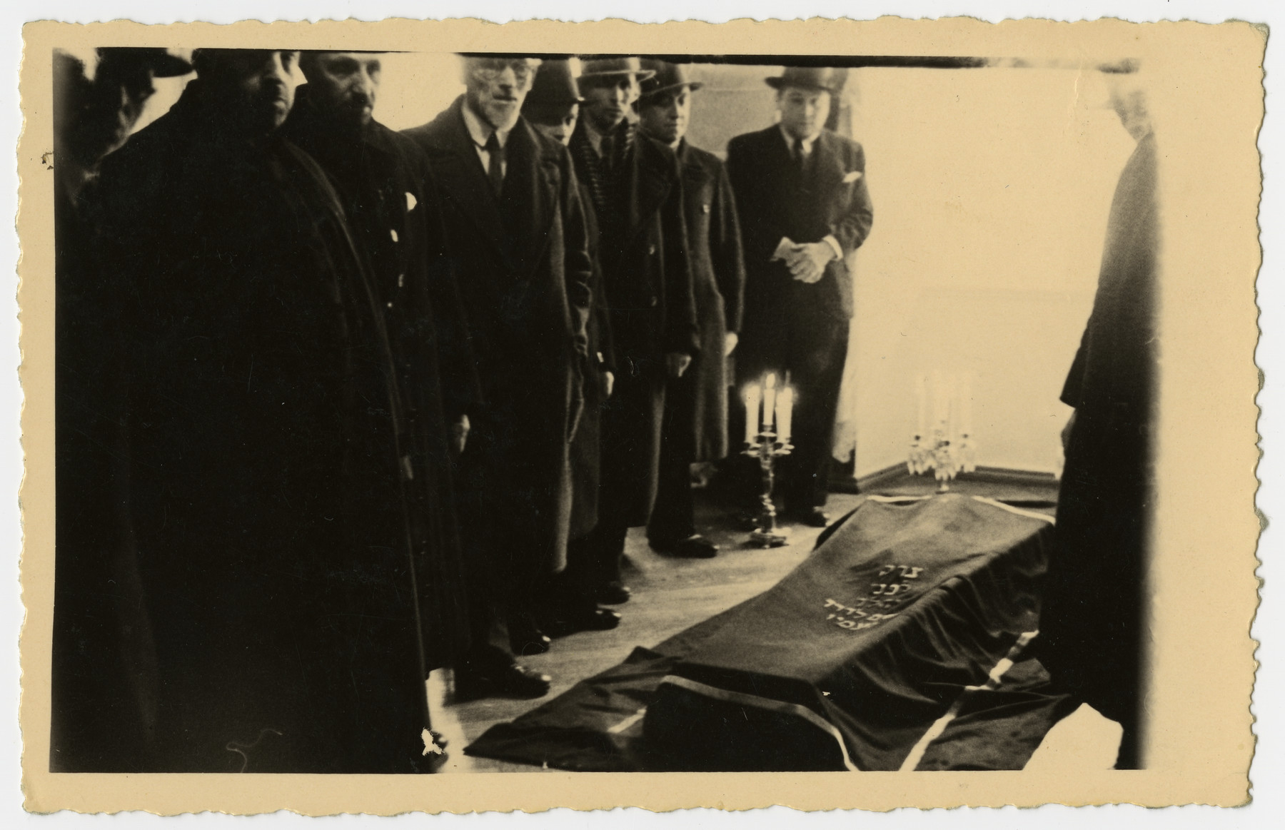 The body of Freida Albin lies in state prior to the funeral.  A group of men stands in attendance.