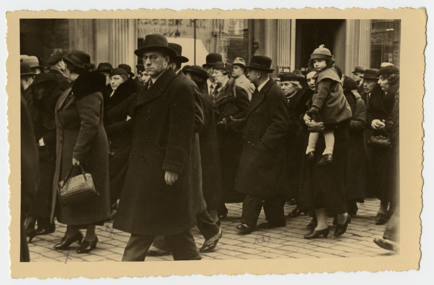 Mourners march down a street of Riga during  the funeral procession for Freida Albin.  Among those pictured are Aunt Zilla (wife of Uncle Aron); Aunt Berta Opapa; Aunt Zerna, behind her Bronja's head, and Mr. Mahler.