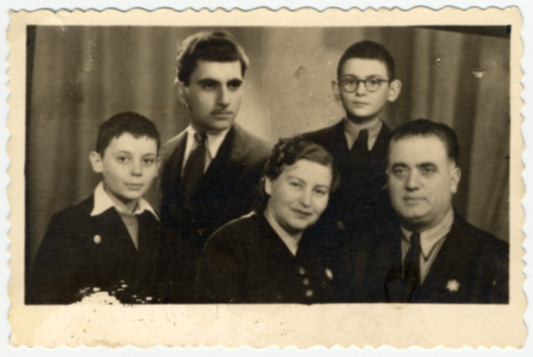 Composite photograph of the Farhis, a Bulgarian Jewish family wearing Stars of David.  The oldest son David was not present for the photograph so his picture was added later.  Also pictured from left to right are Moise, Karolina, Albert and Nissim Farhi.