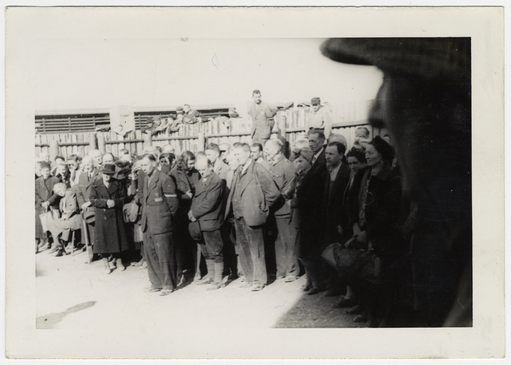 "German civilians are forced to view Buchenwald after liberation.  Original caption:  ""German civilians from Weimar forced to view the crimes of the Nazis""."