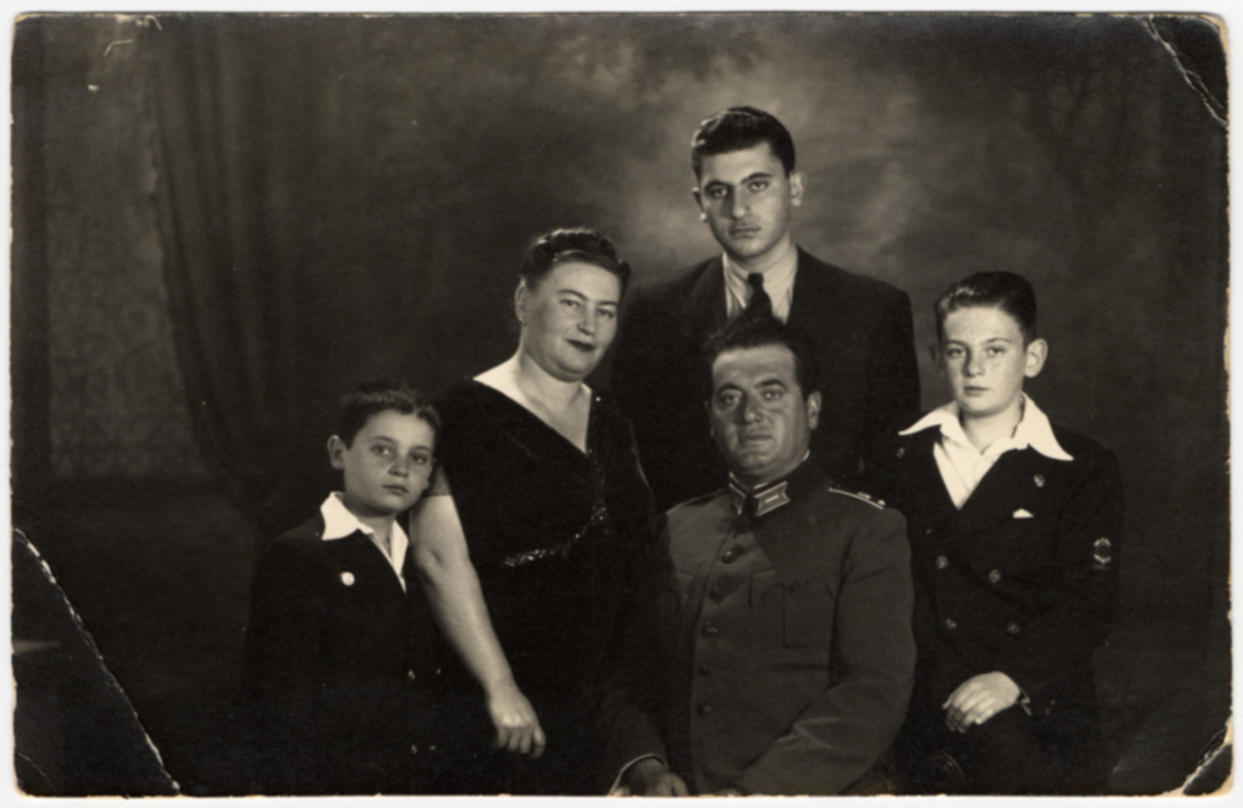 Studio portrait of the Farhis, a Bulgarian Jewish family.  Pictured from left to right are Moise, Karolina, Nissim (wearing his Bulgarian army officer uniform), and Albert.  David Farhi is standing behind his father.